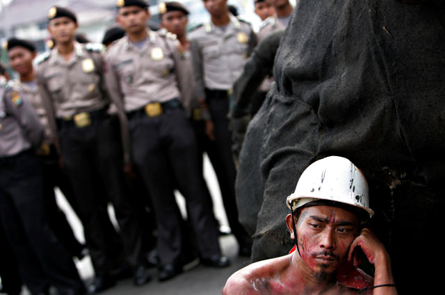 Stop. Listen. Collaborate: a weary-looking Indonesian carpenter listens to speeches at a rally to commemorate International Labour Day. Ed Wray/AP