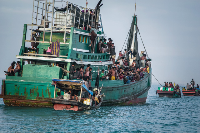 Home and away: Acehnese fishermen help Rohingya migrants into their boat off the coast of Kuala Simpang Tiga. Photo: AFP