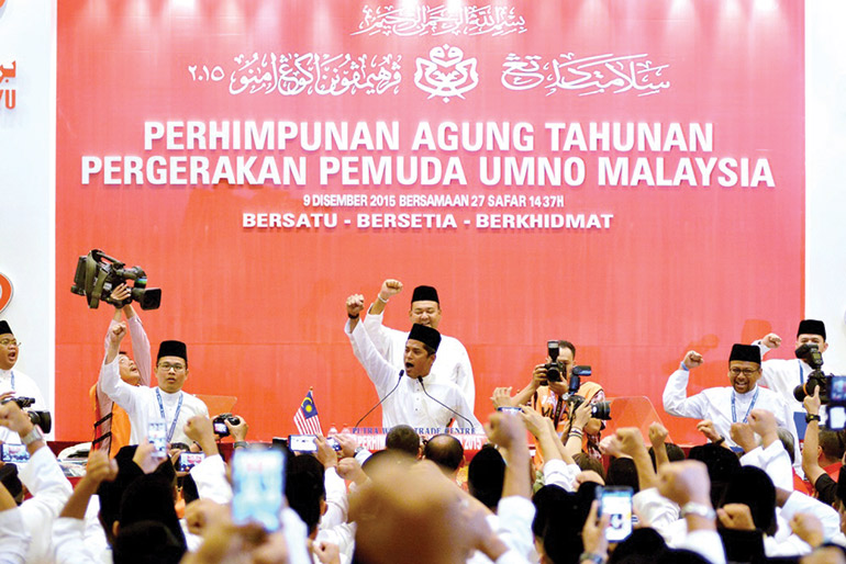 Khairy Jamaluddin leads delegates in a chant at the UMNO Youth general assembly