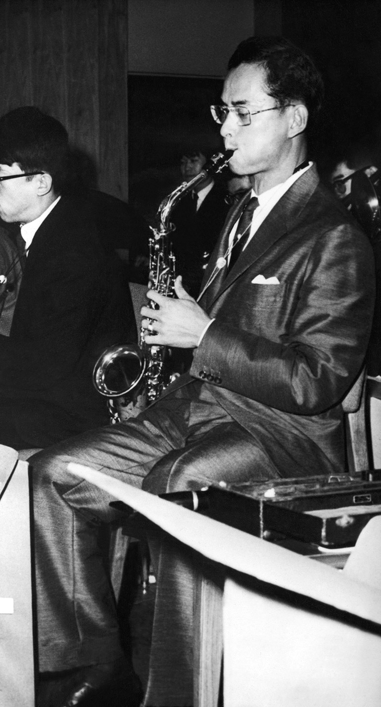 """Sitting in the reed section of a Japanese student Jazz Band, King Bhumibol Adulyadej of Thailand plays a saxophone during a performance of """"Love at Sundown"""", one of his many Jazz compositions, at a farewell dinner party at the state guest house in Tokyo"""