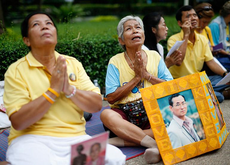 Thai well-wishers pray behind portraits of Thai King Bhumibol Adulyadej at Siriraj Hospital in Bangkok, Thailand, 10 October 2016.