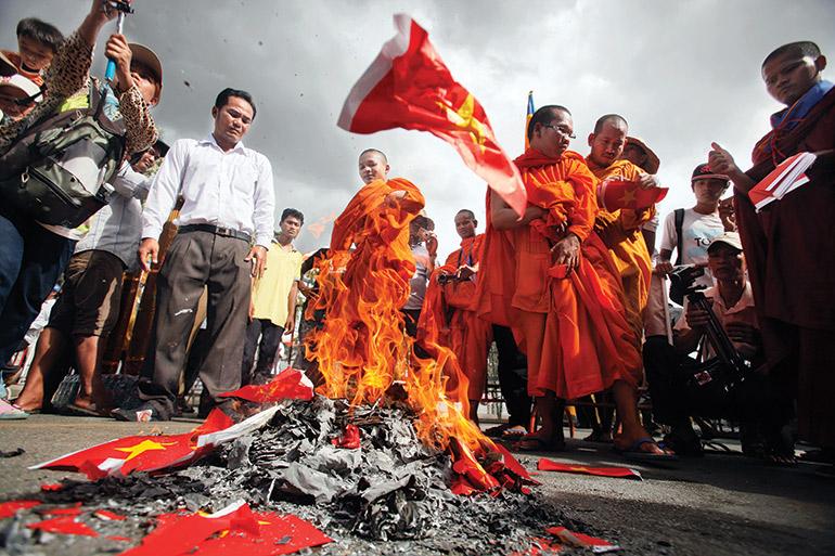 Cambodian Buddhist monks burn Vietnamese flags near the Vietnamese embassy in Phnom Penh