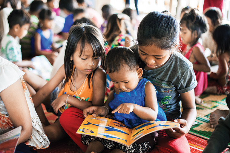 Young children read a picture book during a mobile library session put on by Sipar.