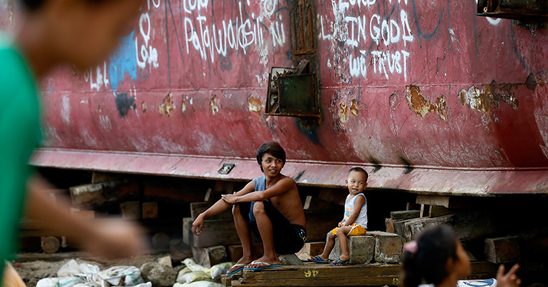 Children play in front of a ship washed ashore by the 2013 Typhoon Haiyan in Anibong village, Tacloban City, Philippines