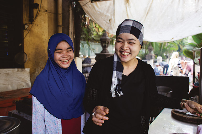 a pair of Cham women show off competing styles of headwear in central Phnom Penh