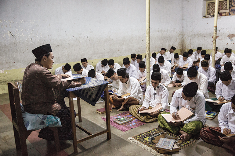 students sit on woven mats on the floor during a class