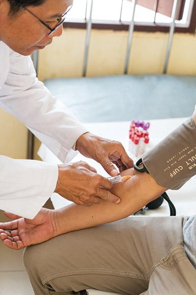 HIV nurse Roeun Man demonstrates a blood test.