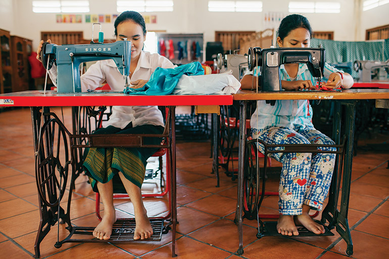 Women sew garments during a lesson at AFESIP's Phnom Penh rescue centre. Photo: Bernardo Salce