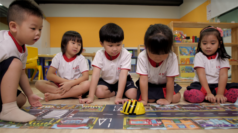 Pre-School students interacting with the Bee Bot