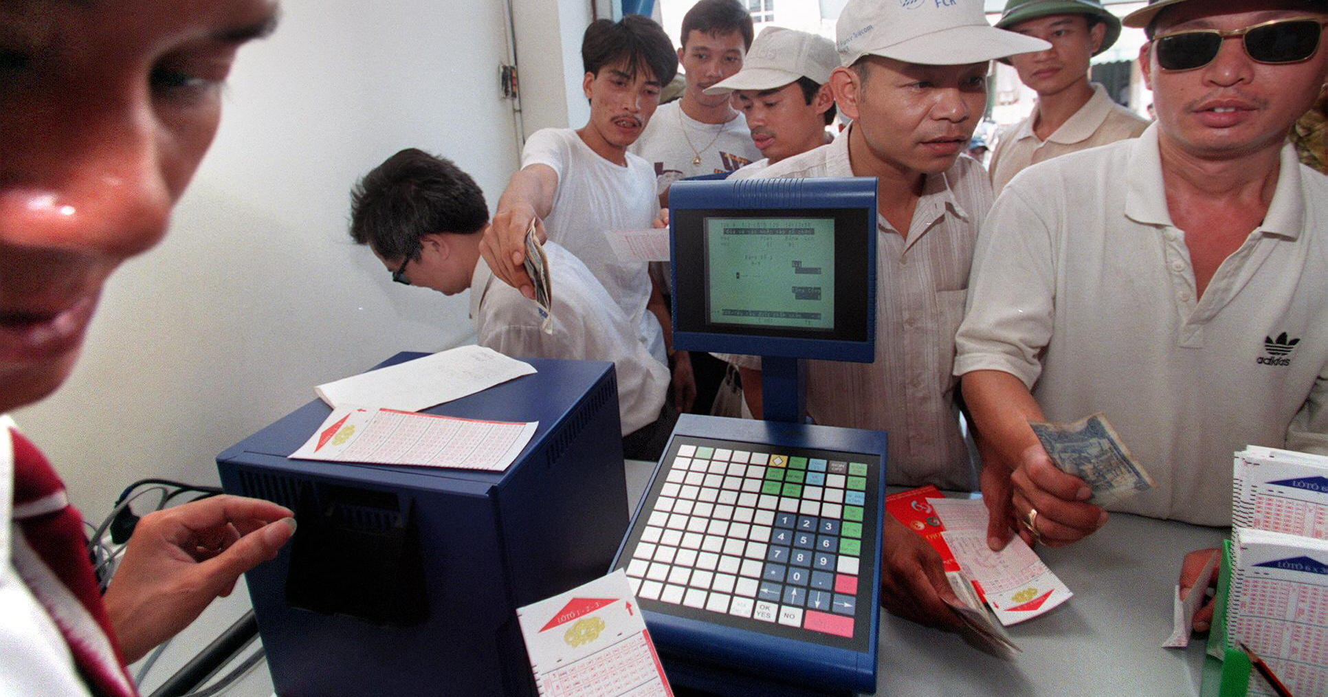 Men buy lottery tickets Photo: Hoang Dinh Nam / AFP