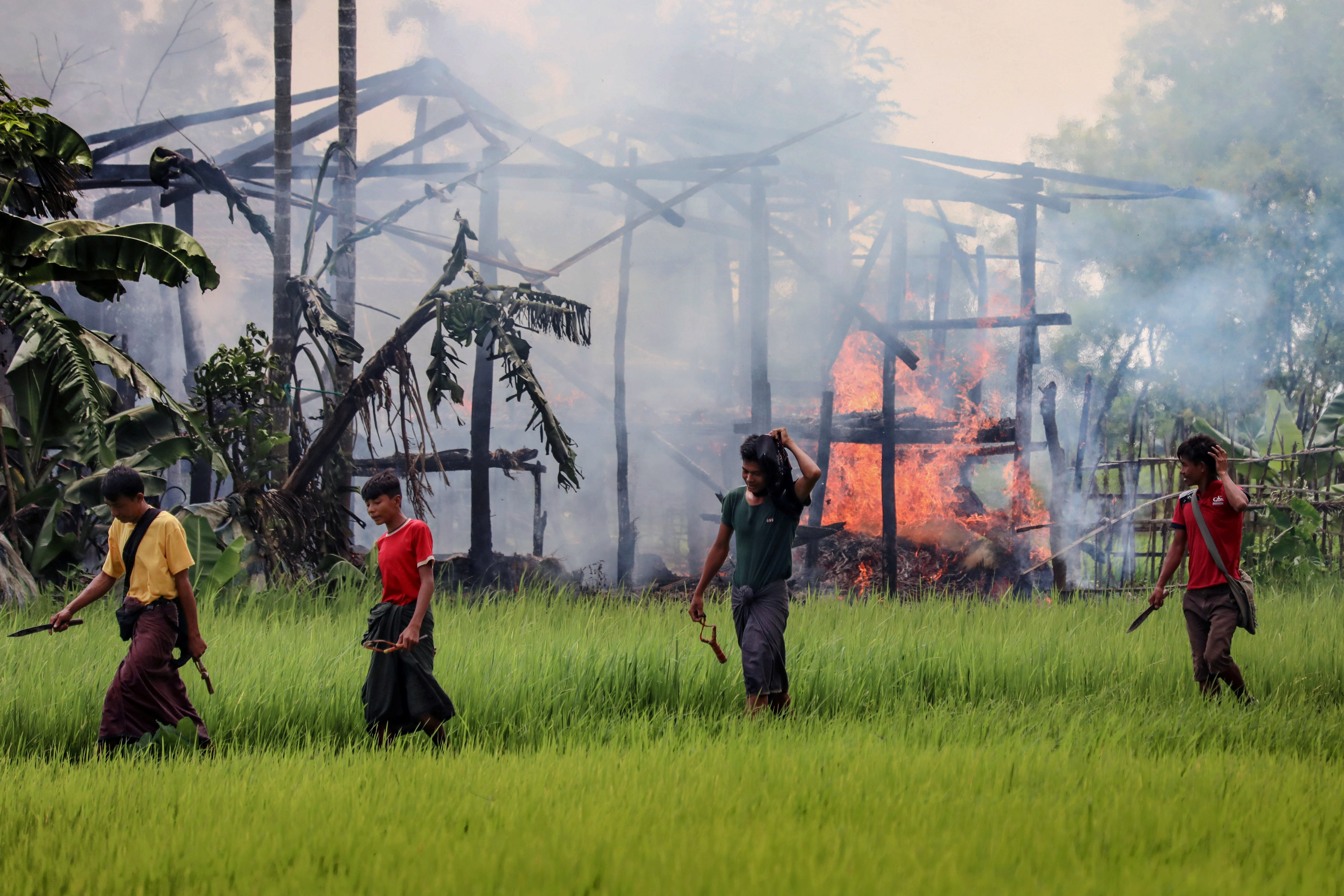 Unidentified men carry knives and slingshots as they walk past a burning house in Gawdu Tharya village near Maungdaw in Rakhine state in northern Myanmar in 2017. Photo: AFP