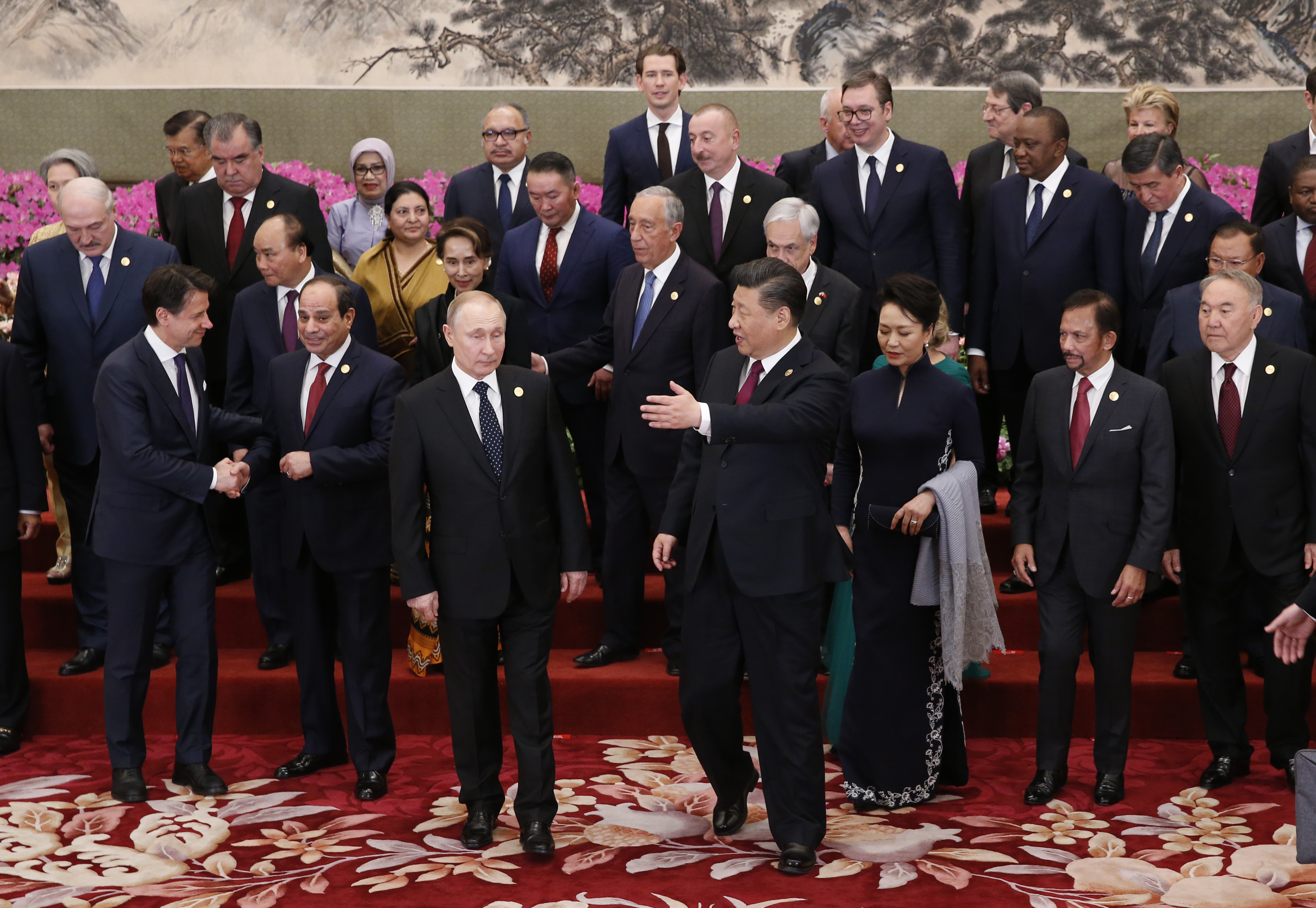 China's President Xi Jinping (C) gestures to Russia's President Vladimir Putin (centre L) after a group photo session at a welcoming banquet for the Belt and Road Forum at the Great Hall of the People in Beijing on April 26, 2019. (Photo by JASON LEE / POOL / AFP)