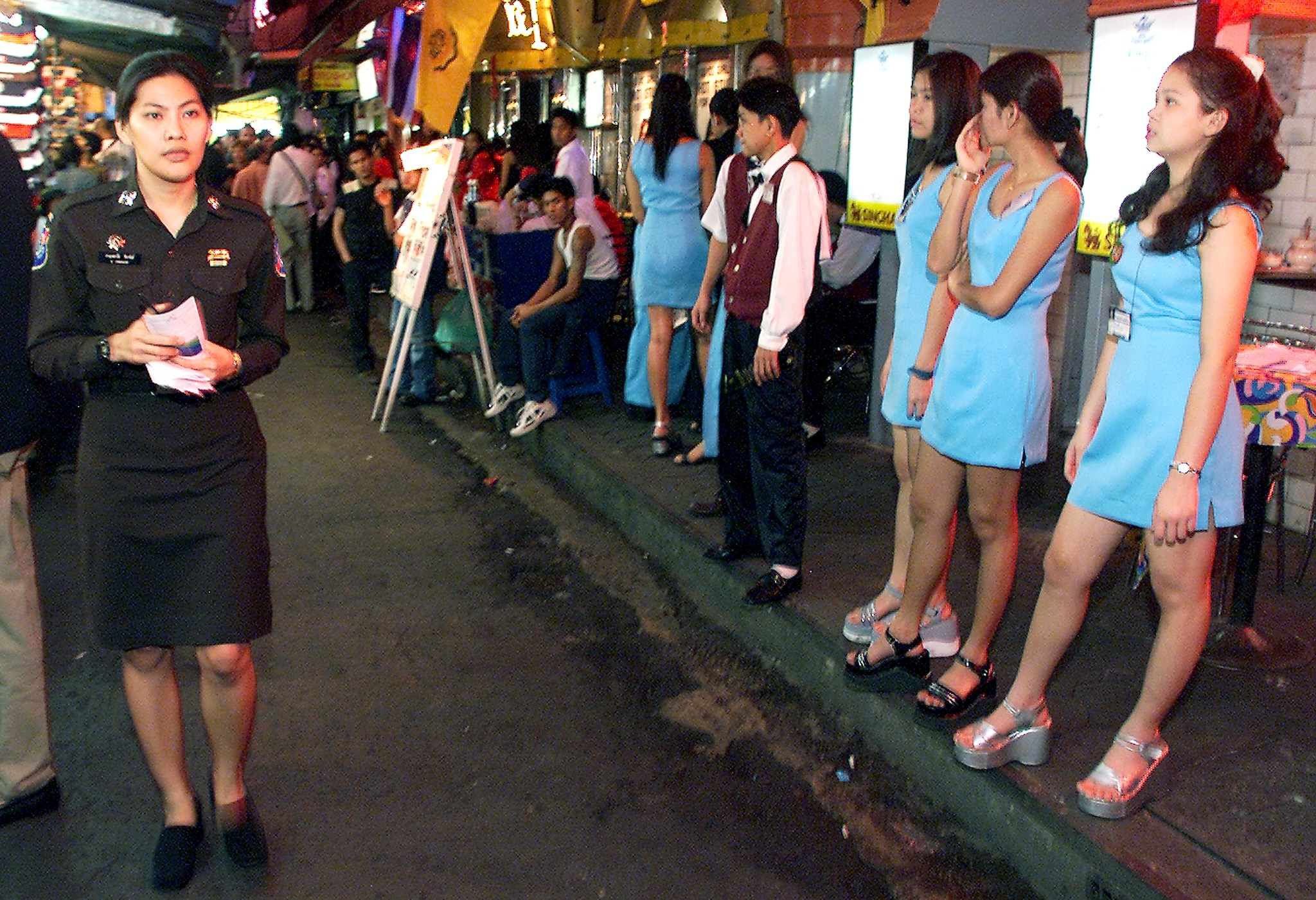 Thai Tourist Police Corporal Kanjanawadee Pongkhunt known as 'Jinny' (L) patrols past Thai bar girls in Bangkok's infamous red-light district of Patpong. Photo: Emmanuel Dunand/AFP