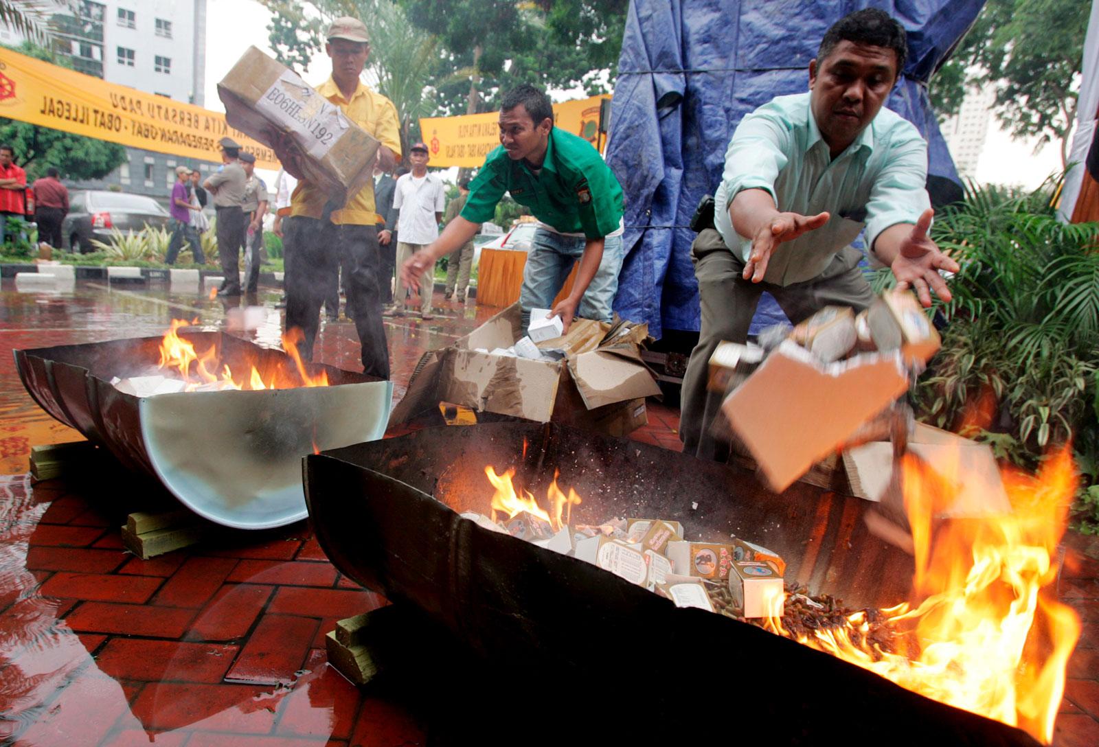 Indonesian policemen burn illegal medicines at Jakarta's police headquarters in late 2007. Photo: EPA/Mast Irha