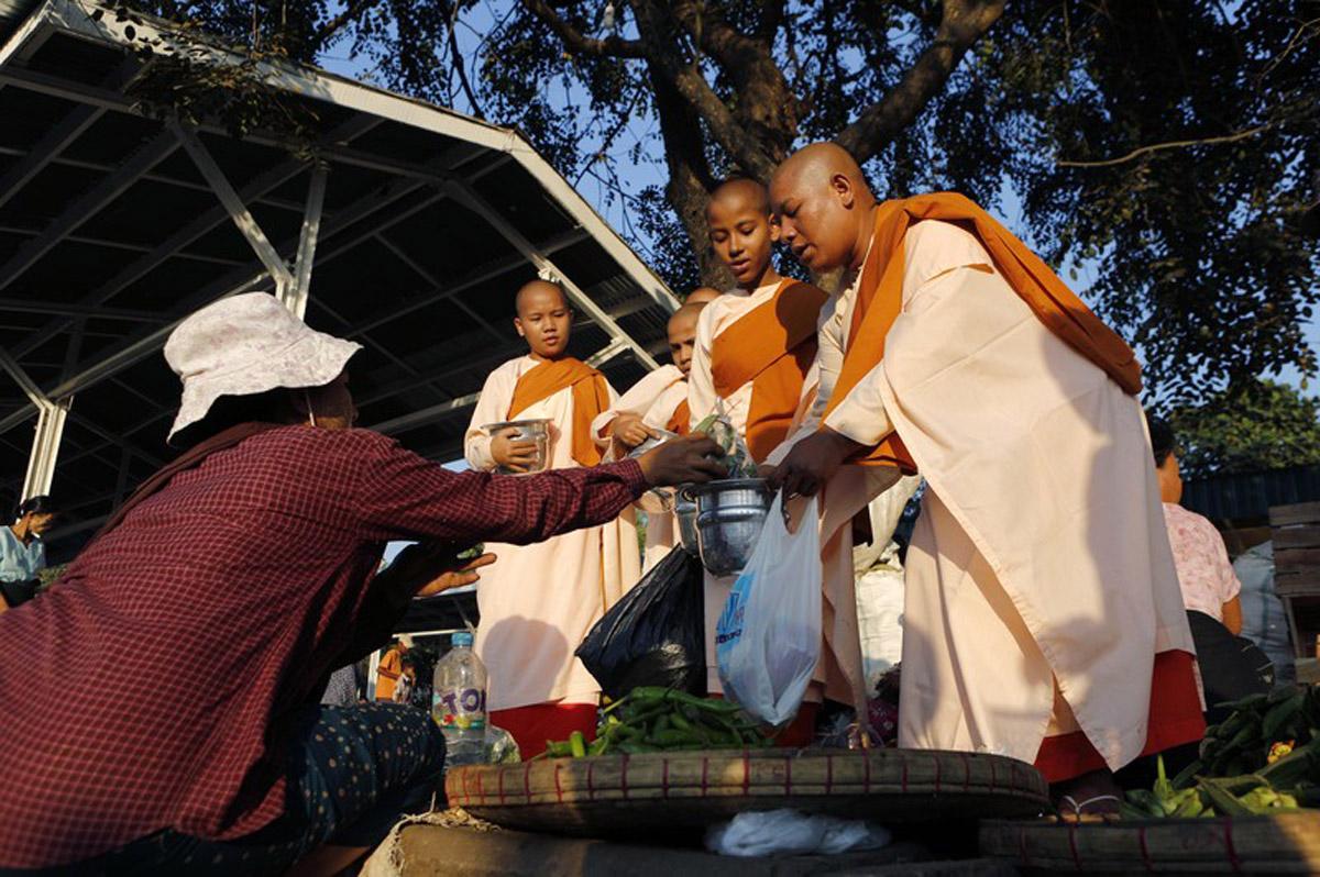Street vendors offer vegetables to Buddhist monks near a train station in Yangon in 2014. Photo: EPA/Lynn Bo Bo