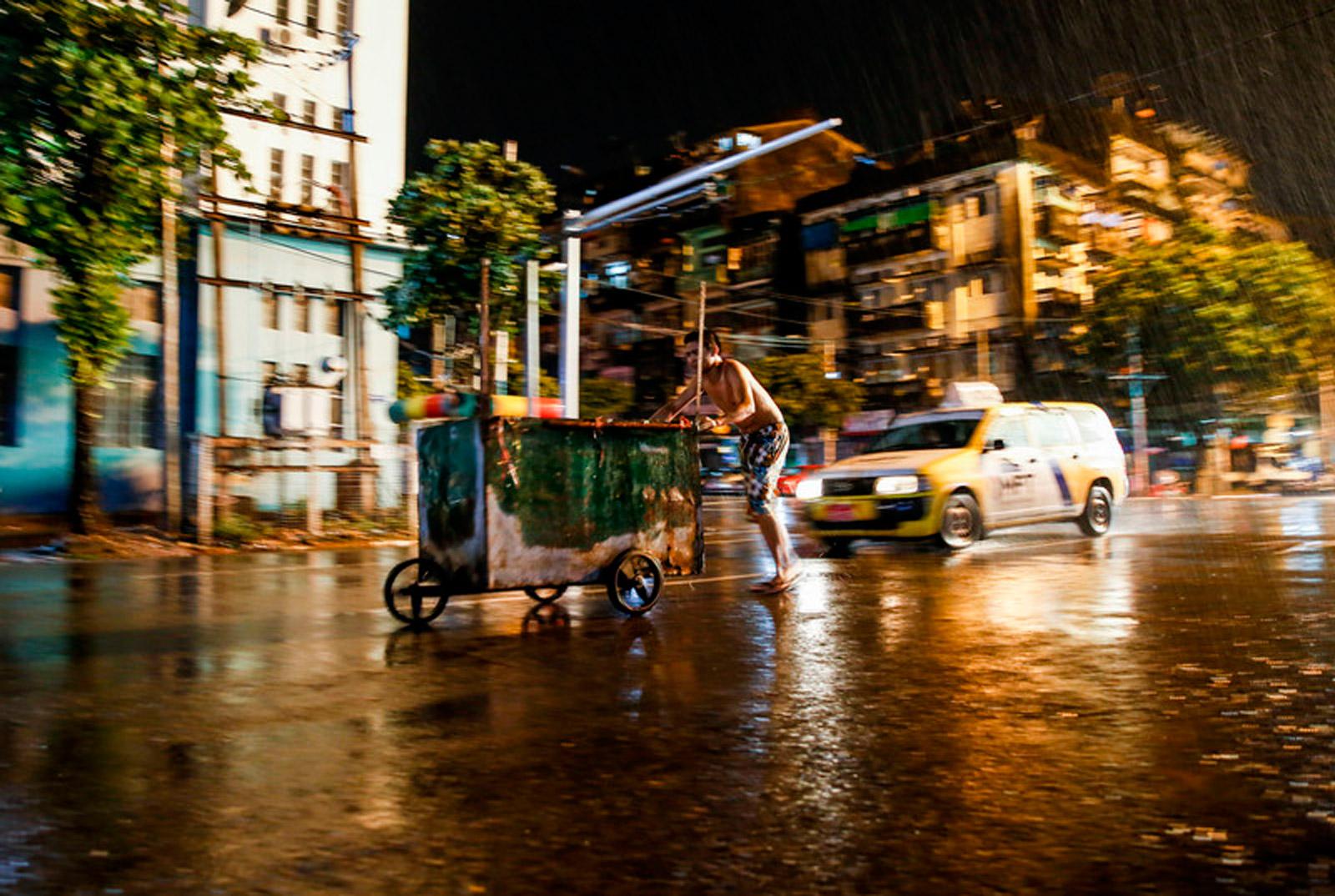Street vendor pulls cart in Yangon during rainy season, June 2017. Photo: EPA/Lynn Bo Bo