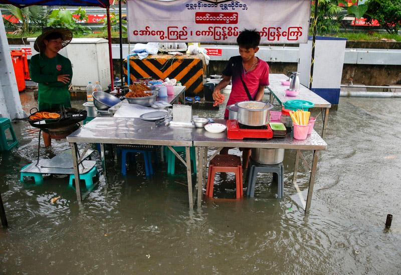 Food stall on flooded Yangon street during June 2017 monsoon rains. Photo: EPA/Lynn Bo Bo