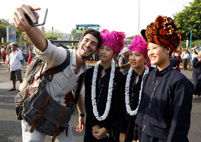 Tourist takes selfie with ethnic Pa-o ethnic women during the Thingyan Water Festival in Yangon in April 2019. Photo: EPA/Nyein Chan Naing